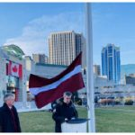 Members of the diplomatic community and Latvian diaspora attended the Latvian flag-raising ceremony. Jim Watson, right, delivers remarks while the ambassador looks on. (Photo: Ülle Baum)