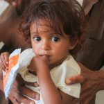 A Yemeni child holds some food from a World Food Programme (WFP) at a WFP-supported nutrition clinic treating malnutrition among children. (Photo: WFP/Issa-Al-Raghi)