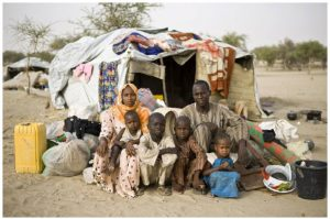 A refugee family — who fled Boko Haram attacks in Nigeria — sit in front of their shelter at the Sayam Forage Refugee Camp in Niger. (Photo: © UNHCR/Hélène Caux)